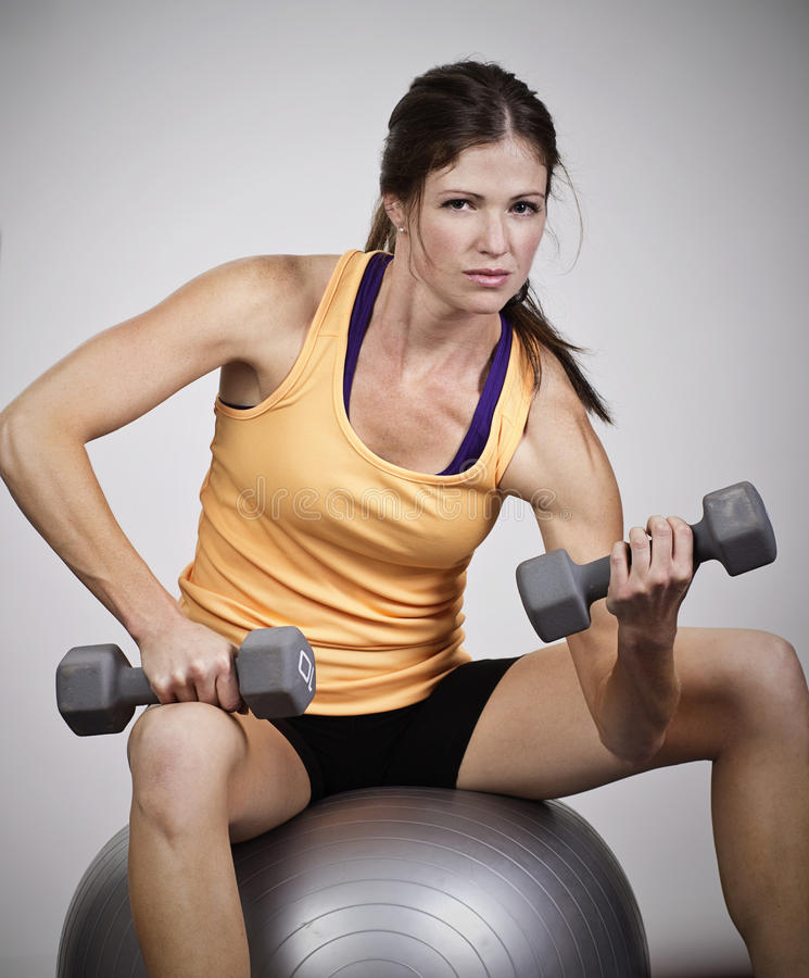 Strong Beautiful Woman Lifting free weights royalty free stock photo