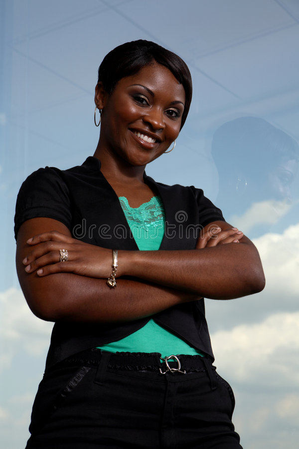 Strong black business woman. Business woman standing by the window royalty free stock photography