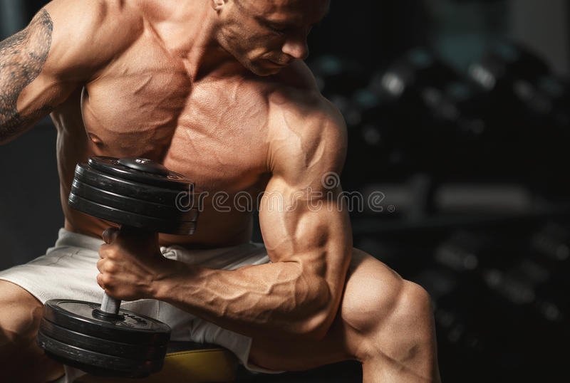 Strong bodybuilder doing exercise with dumbbell stock images