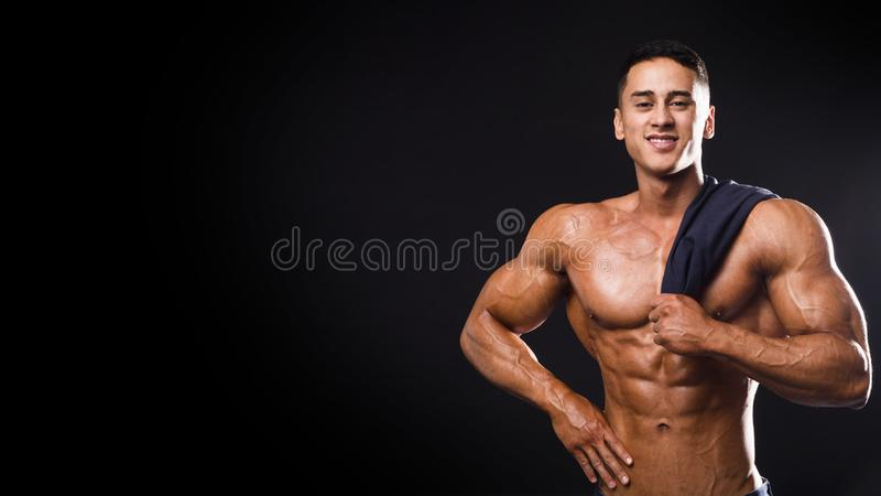 Strong bodybuilder man smiling with perfect abs, pecs, shoulders, biceps, triceps and chest holding a towel. on stock photos