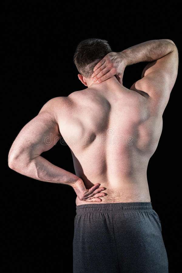 Strong bodybuilder with painful back and neck. On black background stock images