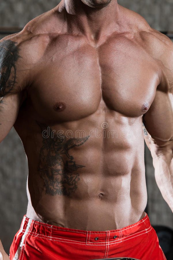 Strong Athletic Man Showing Six Pack Abs. Closeup Stock