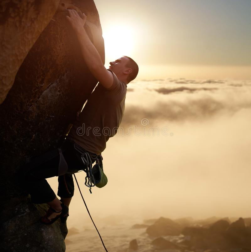 Brave male climber blinded by sunlight on high natural rock wall over gray clouds. Climbing with rope and safety harness royalty free stock images