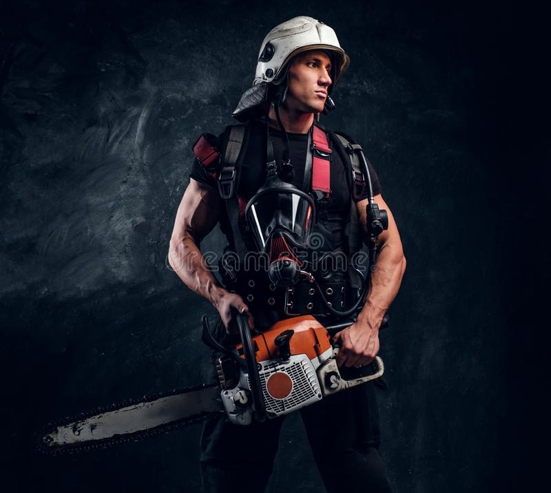 Portrait of strong man with chainsaw and oxygen mask. Strong brave man in helmet is looking away. He has chainsaw in hands and oxygen mask on his chest. Dark stock image