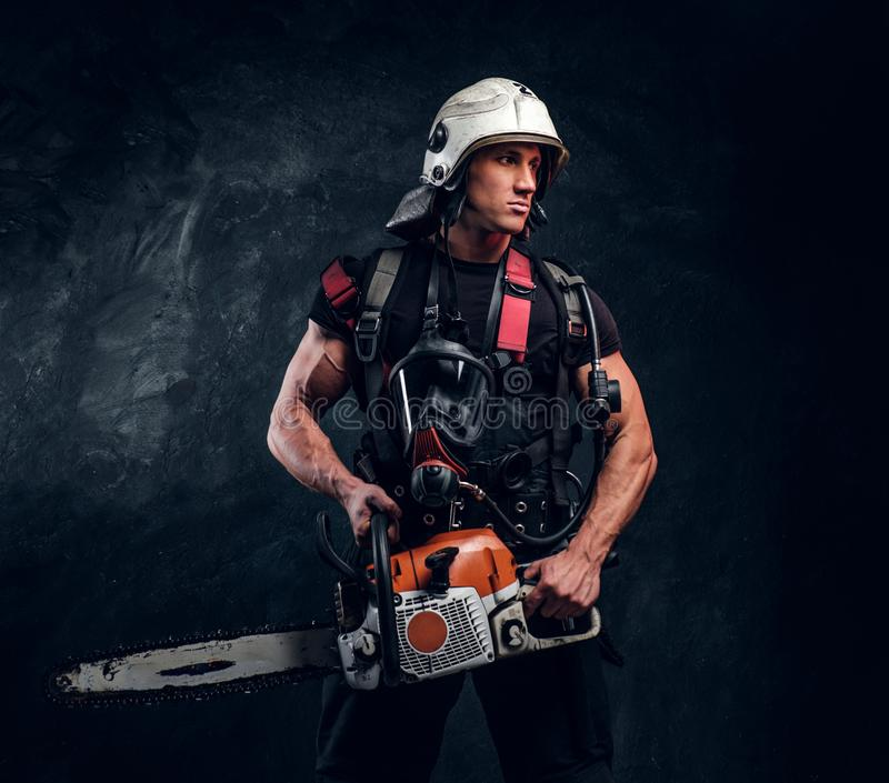 Portrait of strong man with chainsaw and oxygen mask. Strong brave man in helmet is looking away. He has chainsaw in hands and oxygen mask on his chest. Dark royalty free stock photography