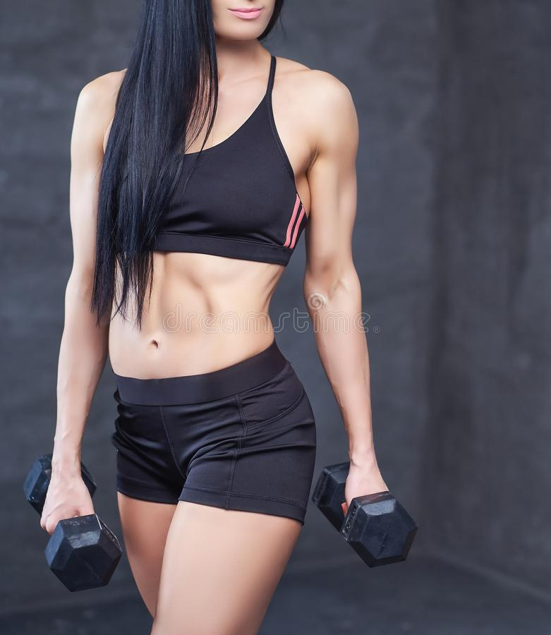 Strong brunette sporty woman in a sportswear doing exercise with dumbbells at a gym. royalty free stock images