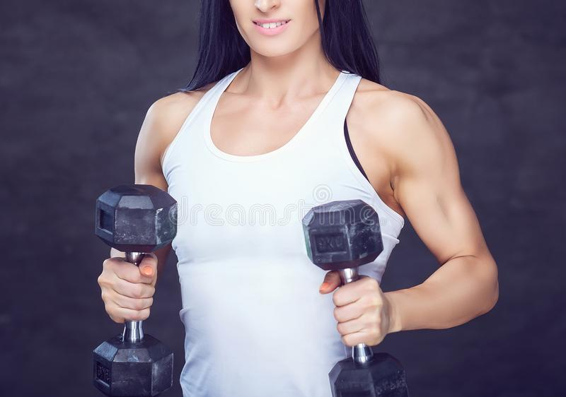 Strong brunette sporty woman in a sportswear doing exercise with dumbbells at a gym. royalty free stock image
