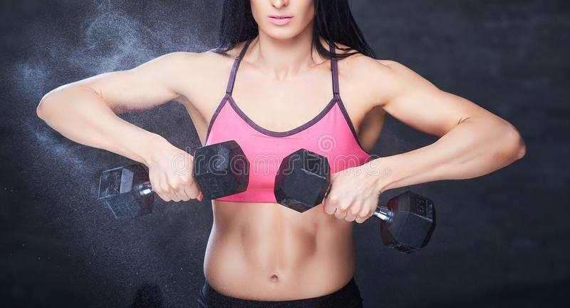 Strong brunette sporty woman in a sportswear doing exercise with dumbbells at a gym. stock photography