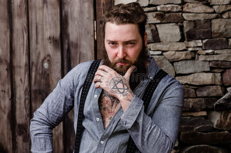 Strong brutal man with a beard and tattoos on his hands dressed in stylish casual clothes stands on the background of stock photos