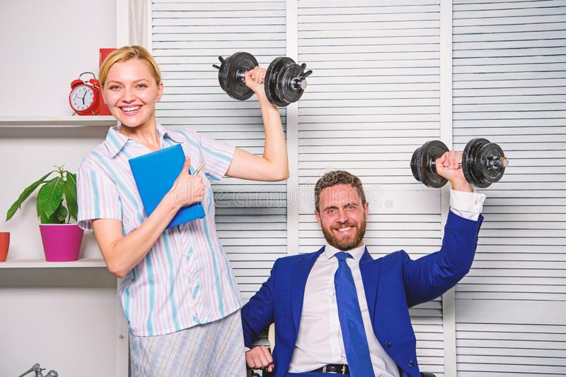 Strong business team. Healthy habits in office. Man and woman raise heavy dumbbells. Strong powerful business strategy. Strong business team. Healthy habits in stock images
