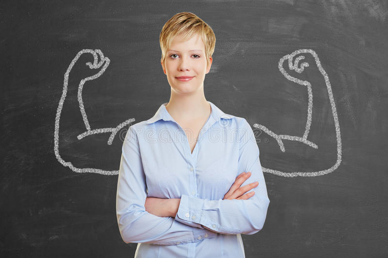 Strong business woman with muscles. Strong business woman with chalk muscles in front of a blackboard royalty free stock images