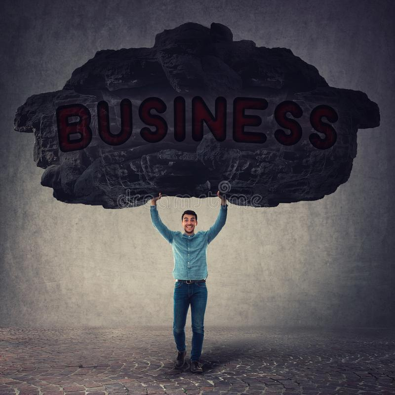 Strong businessman lifting up a huge heavy stone above his head as facing all business problems. Burden concept, effort to carry a stock image