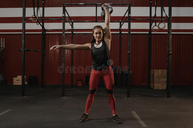 Strong cheerful woman with muscular body exercising with kettlebell while crossfit training royalty free stock images