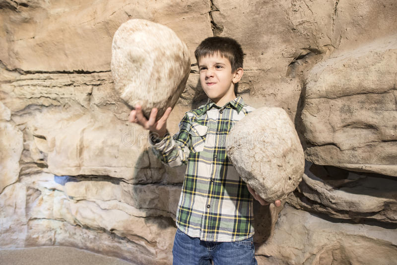 Strong child holds heavy stone. S royalty free stock images