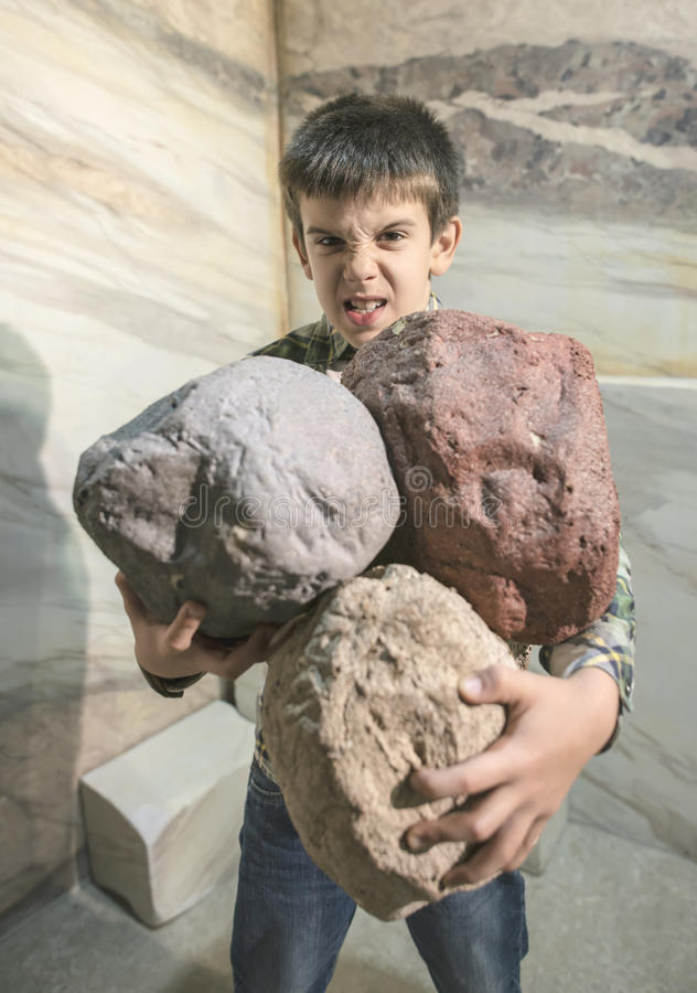 Strong child holds heavy stones stock images