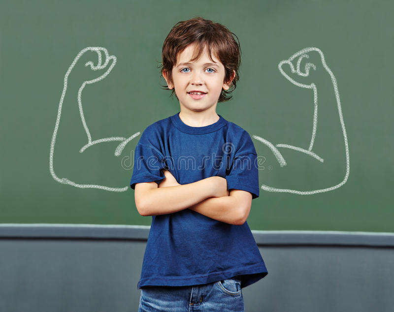 Strong child with muscles in school stock photos