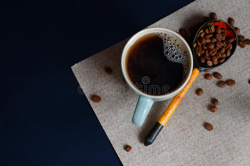 Strong Colombian coffee in a light green cup and whole coffee beans arabica. Top view. royalty free stock photo