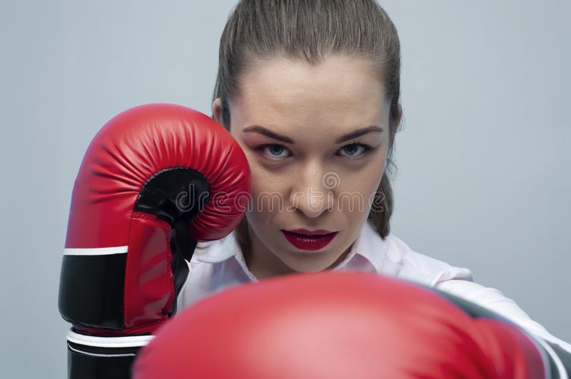 Strong and confident businesswoman wearing blouse and boxing gloves. Take a punch. Strong and confident businesswoman wearing blouse and boxing gloves. Young stock image