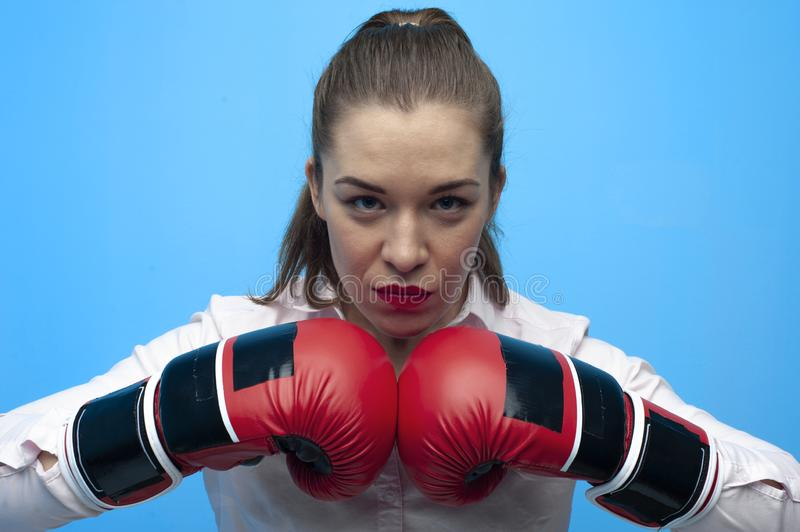 Strong and confident businesswoman wearing blouse and boxing gloves. Young female boss making direct hit stock photo