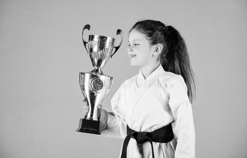 Strong and confident kid. Girl little child in white kimono with belt. Karate fighter child. Karate sport concept. Self. Defence skills. Karate gives feeling of stock photography