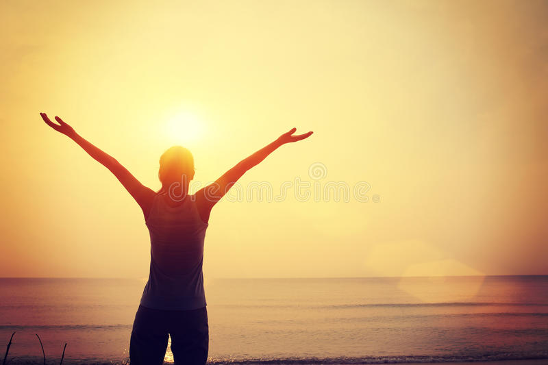 Strong confident woman open arms sunrise seaside royalty free stock photo
