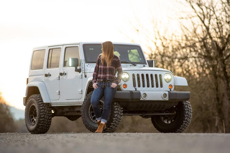 Young woman leaning on SUV on a gravel road. stock image