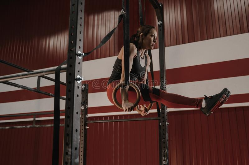 Crossfit woman doing abs exercises on gymnastic rings at the gym. Strong crossfit woman doing abs exercises on gymnastic rings at the gym. Female athlete doing royalty free stock photography