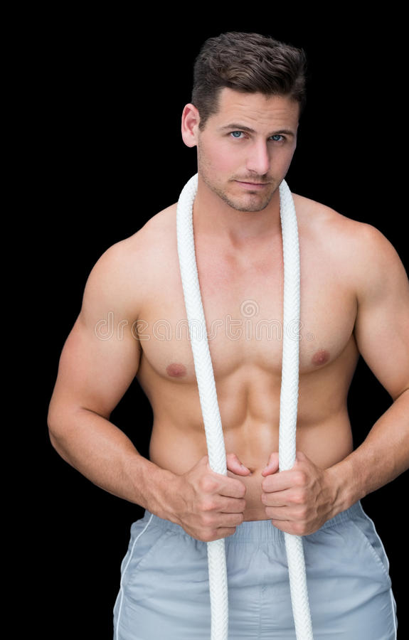 Strong crossfitter posing with rope around neck. On black background stock image