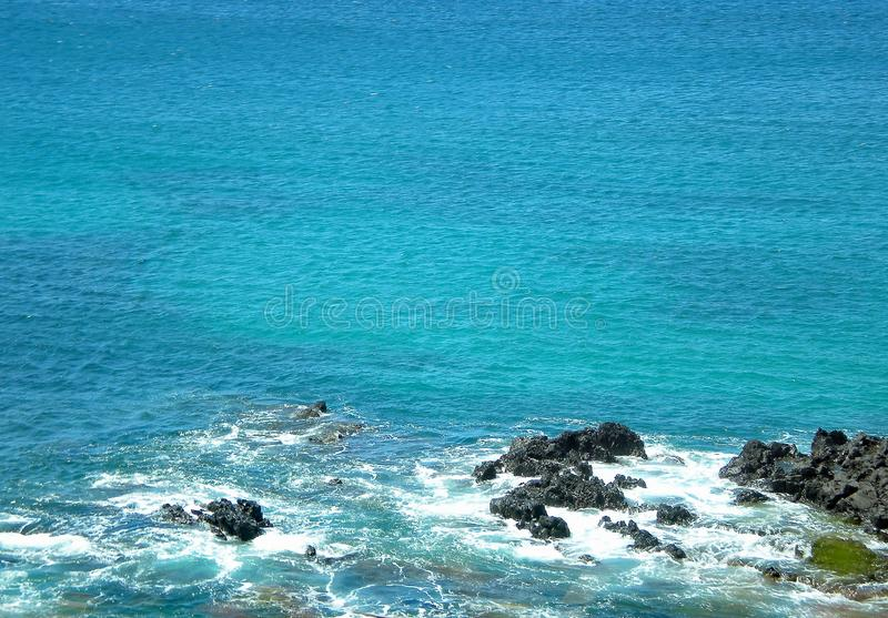 Strong Currents in the Bright Blue Pacific Ocean, Lava Rocks, Sea Foam, and Moss. Oahu Island, Honolulu, Hawaii royalty free stock photo