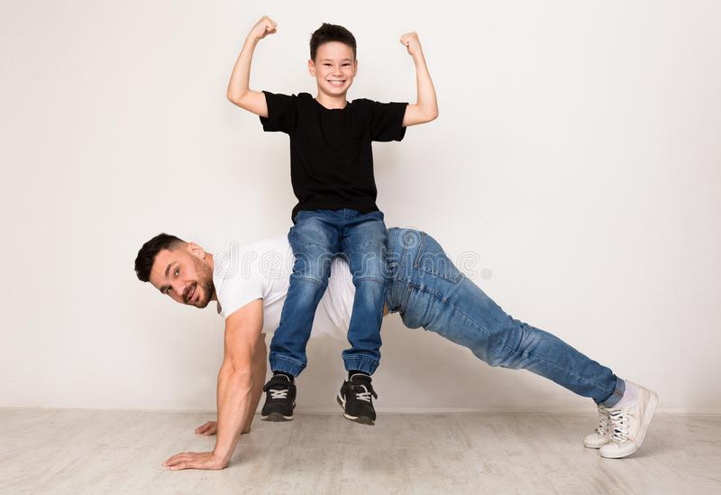 Strong dad doing push ups with son on back. Positive boy showing biceps on camera stock images