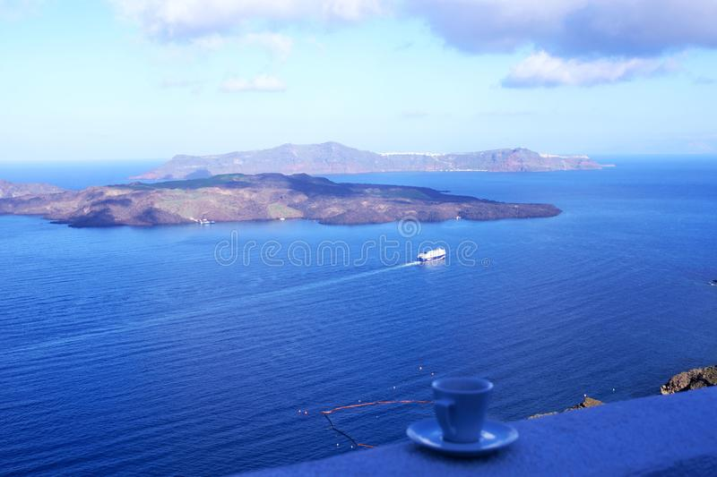 Strong delicious coffee in a white cup with a saucer against the backdrop of the sea and a floating liner. Great start to the day. Santorini, Greece, April 2019 stock images
