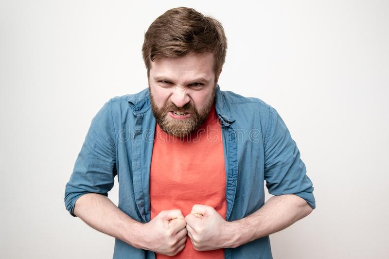 Strong, embittered bearded man clenched his fists and looks furiously at the camera, on a white background. Strong, embittered bearded man clenched his fists and stock images