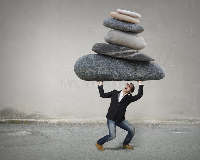 He is strong enough to do it. Young strong man holding huge stone above head royalty free stock photos