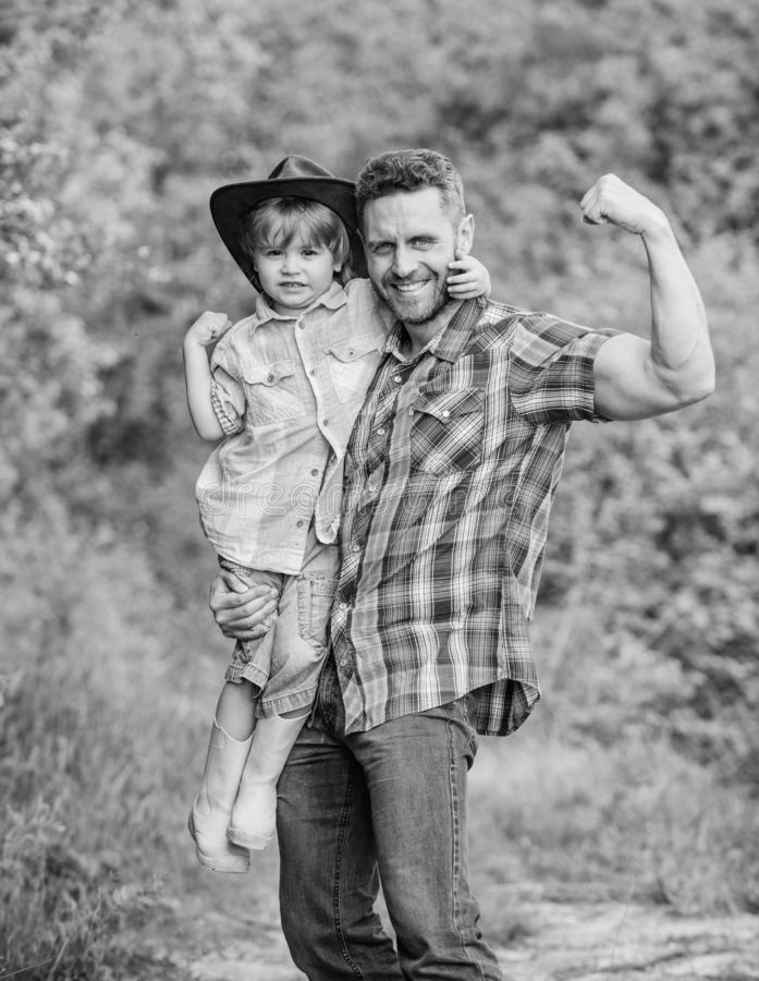 Strong father and son in cowboy hat on ranch. kid in rubber boots. happy man dad in forest. human and nature. family day royalty free stock images