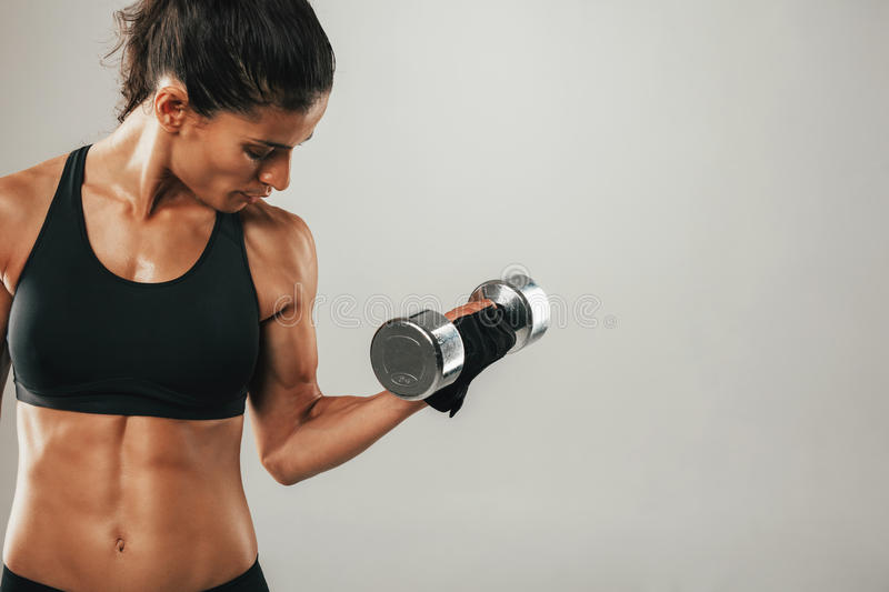 Strong female athlete lifting dumbbell royalty free stock photo