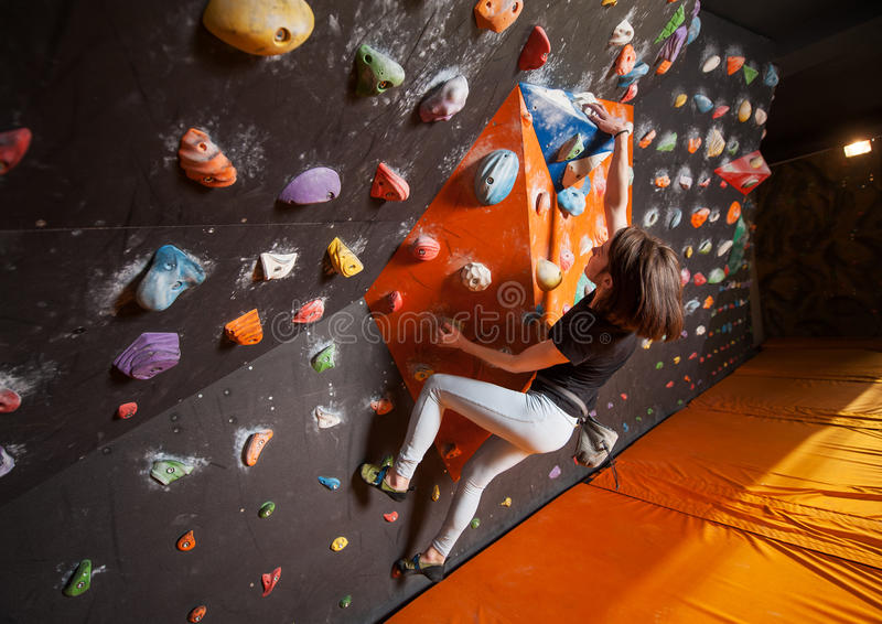 Strong female climber on boulder climbing wall indoor. Young woman climbing up on practicing rock wall indoor stock photography