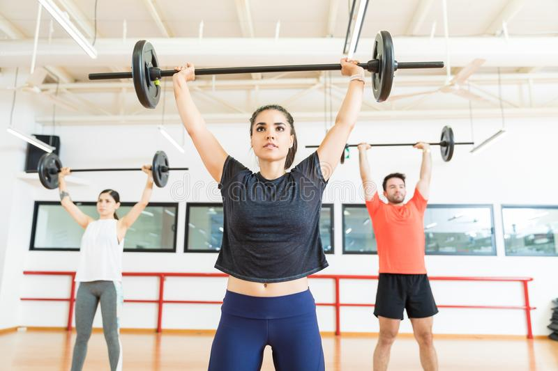 Strong Female Lifting Barbell In Health Club stock image