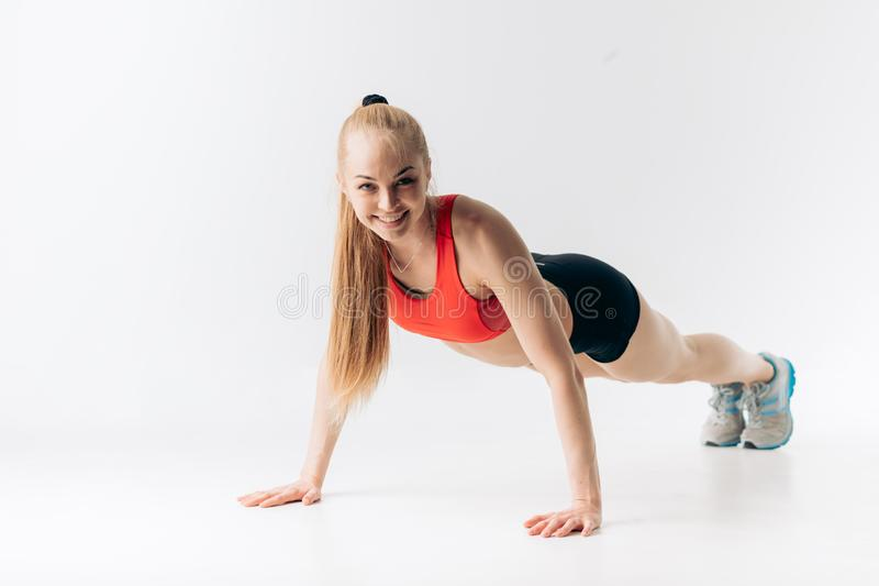 Strong female sportswoman in stylish outfit doing morning exercises. Isolated white background. strength stock image