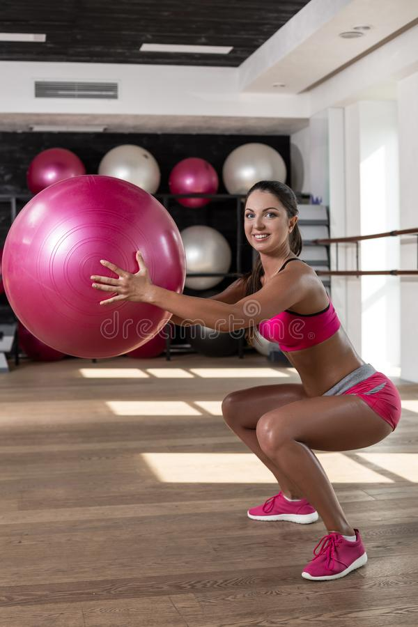 Strong female squatting on fitness mat with weight medicine ball in health club. stock photos