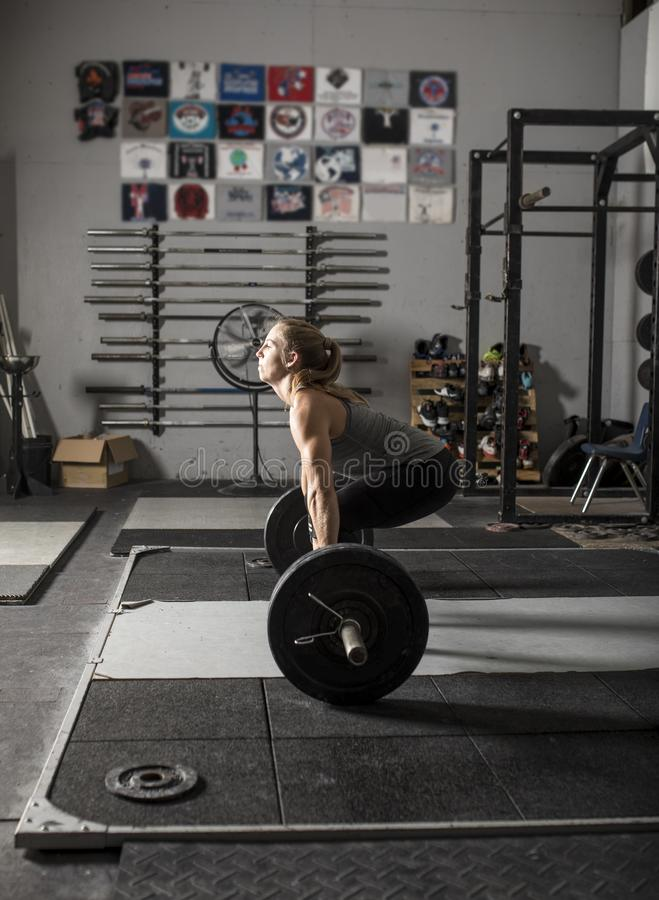 Strong female weight lifter preparing for deadlift in gym royalty free stock image