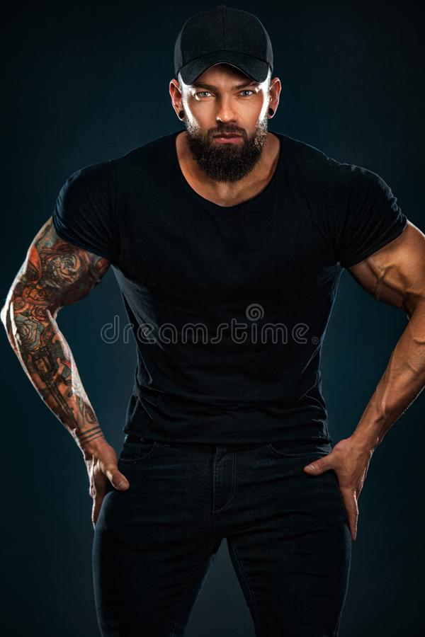 Strong and fit man bodybuilder. Sporty muscular guy athlete. Sport and fitness concept. Men`s fashion. royalty free stock photography