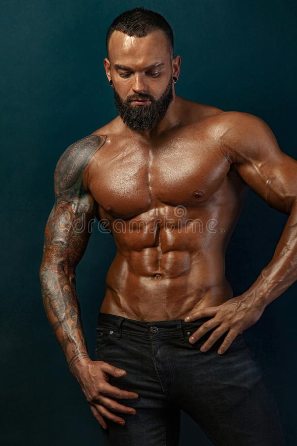Strong and fit man bodybuilder. Sporty muscular guy athlete. Sport and fitness concept. Men`s fashion. stock images