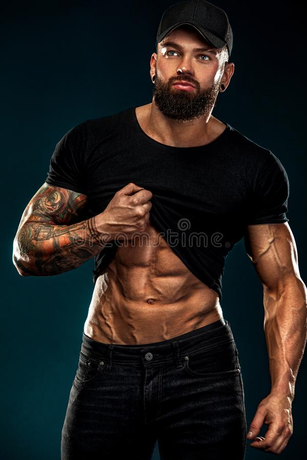 Strong and fit man bodybuilder. Sporty muscular guy athlete. Sport and fitness concept. Men`s fashion. stock photos