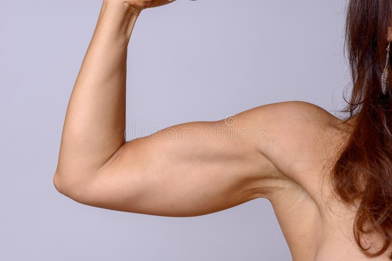 Strong fit mature woman flexing her arm muscles. Strong fit mature woman clenching her fist and flexing her arm muscles showing off her toned biceps over a grey royalty free stock image