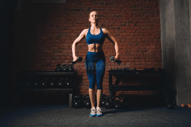 Strong fit sexy blonde woman exercising with dumbbells stock images