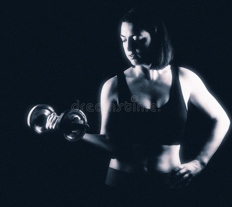Strong fit woman biceps curling stock photo