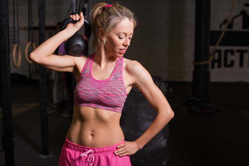 Strong and fit woman lifting weights stock photo