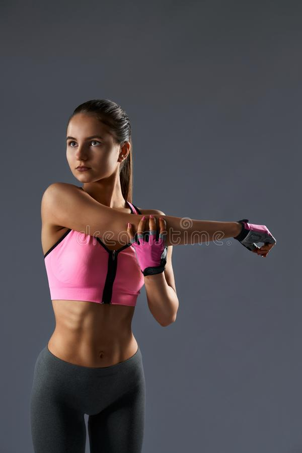 Strong fit woman stretching her arms before doing exercises royalty free stock images