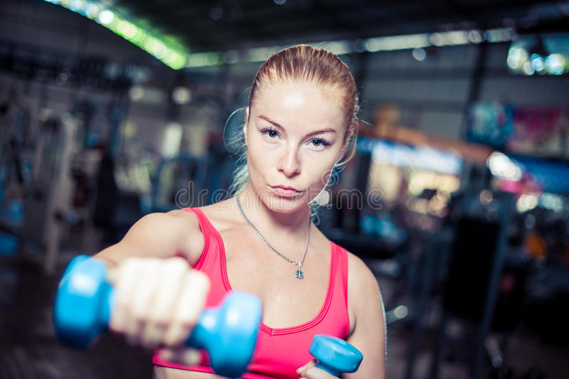 Strong fitness girl with dumbbells. Attractive woman in gym. Caucasian blond model with long hair royalty free stock photo