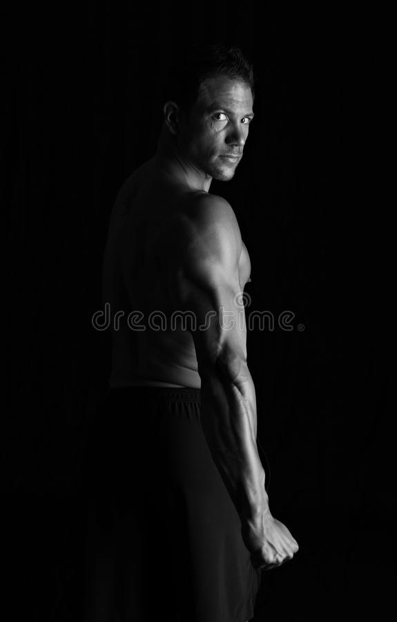 Strong fitness man flexing stock images